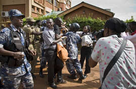 FILE - Reporters and members of Uganda's Human Rights Network for Journalists struggle with police during a protest in downtown Kampala, Uganda, May 28, 2013.