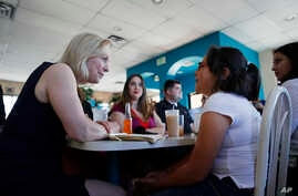 FILE - Democratic presidential candidate Sen. Kirsten Gillibrand (L) speaks with Alexa Arredondo, 9, while meeting with community activists on immigration issues at a restaurant, May 6, 2019, in Las Vegas.