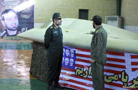 FILE - An undated picture received on Dec 8, 2011, shows a member of Iran's revolutionary guard (R) pointing at the U.S. RQ-170 unmanned spy plane as he speaks with Amirali Hajizadeh, a revolutionary guard commander, at an unspecified location in Ir...