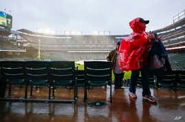 Baseball fans wait out a rain delay before a baseball game between the Oakland Athletics and the Texas Rangers, April 13, 2019, in Arlington, Texas. Tornadoes from the storm system left two children dead and several other people injured.