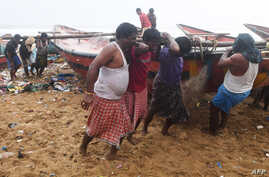 Indian fishermen pull a boat to higher ground on a beach in Puri in the eastern Indian state of Odisha on May 2, 2019, as cyclone Fani approaches the Indian coastline.