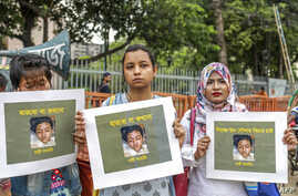 FILE - Bangladeshi women hold placards and photographs of schoolgirl Nusrat Jahan Rafi at a protest in Dhaka, April 12, 2019, following her murder by being set on fire after she had reported a sexual assault.