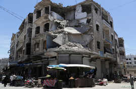 People walk past a damaged building in the city of Idlib, Syria, May 25, 2019.