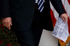 "FILE - President Donald Trump holds papers with handwritten notes that say ""they want to impeach me,"" as he walks from the Oval Office to speak in the Rose Garden of the White House in Washington, May 22, 2019."