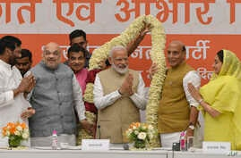 Bharatiya Janata Party (BJP) President Amit Shah (2nd-L) and cabinet members present a garland to Indian Prime Minister Narendra Modi at a function to thank cabinet members for their service in the term that is about to end, in New Delhi, India, May ...