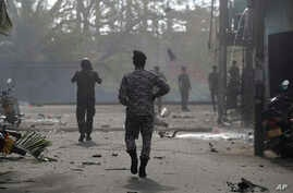 Sri Lankan security forces approach the site after a vehicle parked near St. Anthony's shrine exploded in Colombo, Sri Lanka, Monday, April 22, 2019.