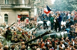FILE - Czech youngsters holding Czechoslovakian flags stand atop of an overturned truck as other Prague residents surround Soviet tanks in downtown Prague on Aug. 21, 1968, as a Soviet-led invasion by the Warsaw Pact armies crushed the so-called Prag...