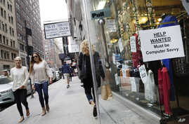 """FILE - A """"Help Wanted"""" sign hangs in a store window in New York City, Oct. 1, 2015."""