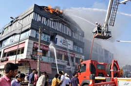 Firefighters work to douse flames on a building in Surat, in the western Indian state of Gujarat, May 24, 2019. At least 19 teenage students were killed in a fire in a four-story building, police said.