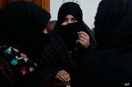 FILE - In this Feb. 18, 2019, photo, Alissa, who faced domestic violence, center, speaks during an interview with the Associated Press at a women's shelter office in Herat, Afghanistan.
