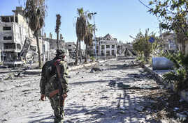 FILE - A member of the Syrian Democratic Forces (SDF) walks through a heavily damaged street leading to an Armenian church in Raqqa, Syria, Oct. 18, 2017.