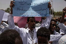 A man holds a banner calling for people who killed protesters to be punished, during a march by members of the Sudanese medical profession syndicate, at the sit-in inside the Armed Forces Square, in Khartoum, April 17, 2019.