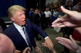 FILE - FILE - In this Aug. 11, 2015, file photo, Republican presidential candidate Donald Trump meets supporters after addressing a GOP fundraising event in Birch Run, Mich.