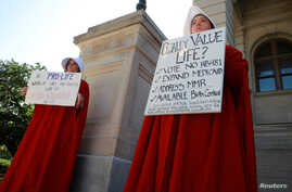 """April Houston and Lara Martin hold signs while dressed as Handmaids in protest of Georgia's anti-abortion """"heartbeat"""" bill at the Georgia State Capitol in Atlanta, Georgia, U.S., May 7, 2019."""