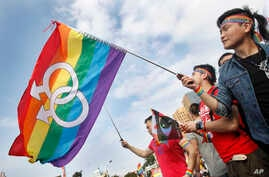 FILE - Supporters of LGBT wave rainbow flags during a rally supporting a proposal to allow same-sex marriage, in Taipei, Taiwan, Dec. 10, 2016.