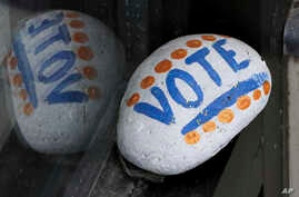 """FILE - A stone painted with the word """"VOTE"""" rests on the window sill of an art gallery in Peterborough, N.H., March 22, 2019. More than half of Americans want major changes to the system of government."""