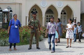 A Sri Lankan government soldier secures the premises of a Catholic church as devotees leave after Sunday Mass in Colombo, Sri Lanka, May 12, 2019.