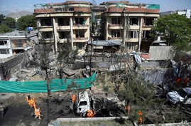 Afghan municipality workers clean debris in front of the damaged buildings a day after Taliban fighters attacked the offices of a U.-based aid organization in Kabul, May 9, 2019