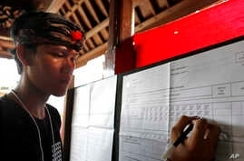 """An electoral worker checks a vote for presidential candidate Joko """"Jokowi"""" Widodo during the vote counting at a polling station in Bali, Indonesia, April 17, 2019."""