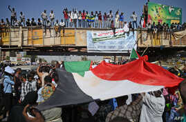 """Sudanese protesters wave a national flag during a """"million-strong"""" march outside the army headquarters in the capital Khartoum April 25, 2019."""