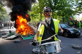 A man bangs a drum in front of a fire on the street during a yellow vest demonstration in Paris, Apr. 20, 2019.