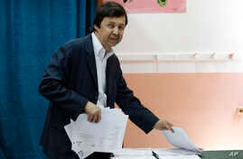 FILE - Said Bouteflika, the brother of then-Algerian President Abdelaziz Bouteflika, takes ballots before voting in Algiers. The influential younger brother of Algeria's former longtime president was detained Saturday May 4, 2019, for questioning alo...