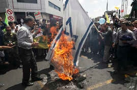 Iranian demonstrators burn a representation of the Israeli flag during their annual protest to mark Quds, or Jerusalem Day, in Tehran, May 31, 2019.