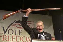 """FILE - In this Monday, Oct. 21, 2002 file photo, National Rifle Association President Charlton Heston holds up a rifle as he addresses gun owners during a """"get-out-the-vote"""" rally in Manchester, N.H."""