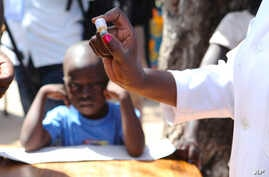 A health worker prepares to administer an oral cholera vaccination to a child at a camp for displaced survivors of cyclone Idai in Beira, Mozambique, April 3, 2019.