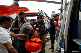 Officials carry the body of a victim from a small aircraft belonging to Summit Air that crashed into a helicopter parked at Lukla airport before transport to at a hospital in Kathmandu, Nepal, April 14, 2019.