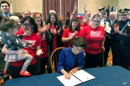 FILE -  Cheers erupt as Rhode Island Gov. Gina Raimondo signs an executive order, Feb. 26, 2018, in Warwick, R.I., to establish a new policy to try to keep guns away from people who show warning signs of violence.