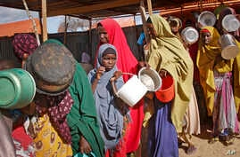 FILE - Newly-arrived women who fled drought queue to receive food distributed by local volunteers at a camp for displaced persons in the Daynile neighborhood on the outskirts of the capital Mogadishu, in Somalia, May 18, 2019.