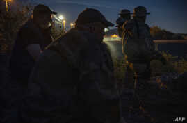 FILE - Members of a militia patrol the U.S.-Mexico border in Sunland Park, New Mexico, March 20, 2019.