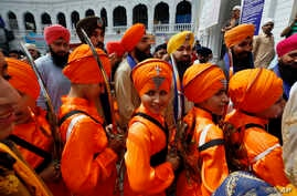 Sikh youth, in traditional dress and holding ceremonial swords, while attending a ceremony during the Vasakhi festival, at the shrine of Gurdwara Punja Sahib, the second most sacred place for Sikhs, in Hasan Abdal, some 50 kilometers from Islamabad, ...