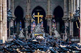 A view of the cross and sculpture of Pieta by Nicolas Coustou in the background of debris inside Notre Dame, in the aftermath of a fire that devastated the cathedral in Paris, France, April 16, 2019.
