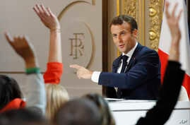 Members of the media raise their hands as French President Emmanuel Macron answering questions during a media conference at the Elysee Palace, April 25, 2019 in Paris.