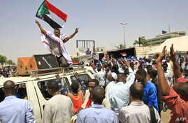 Sudanese protesters, waving national flags, take part in a sit-in outside the army headquarters in Khartoum, May 5, 2019.