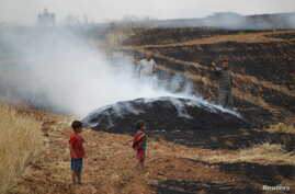 FILE - A man gestures as smoke rises from a burning farmland targeted by what activists said were airstrikes by forces loyal to Syria's President Bashar al-Assad in Maarshmarin village in Idlib countryside, May 24, 2015.