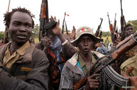SPLA-IO  rebels hold up guns in Yondu, the day before an assault on government SPLA (Sudan People's Liberation Army) soldiers in the town of Kaya, on the border with Uganda, South Sudan, Aug. 25, 2017.