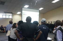 People watch results during a test of the Election Results Management System as votes trickled in from various constituency centers.