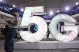 A man stands next to a sign of 5G at the Tencent Global Digital Ecosystem Summit in Kunming, Yunnan province, China, May 23, 2019.