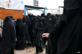 FILE - Women line up for aid supplies at al-Hol camp in Hassakeh province, Syria, March 31, 2019.