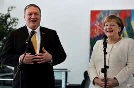 U.S. Secretary of State, Mike Pompeo, left, and German Chancellor Angela Merkel, right, address the media during a joint statement prior to a meeting at the chancellery in Berlin, Germany, May 31, 2019.