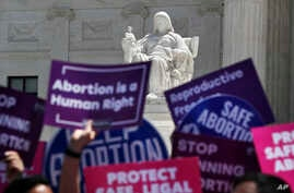 FILE - People hold up signs in favor of legal abortion during a protest against abortion bans, May 21, 2019, outside the Supreme Court in Washington.