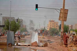 Smoke rises behind barricades laid by protesters to block a street in the Sudanese capital Khartoum to stop military vehicles from driving through the area on June 5, 2019.