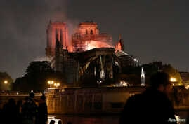 Firefighters douse flames from the burning Notre Dame Cathedral as people look on in Paris, France, April 15, 2019.