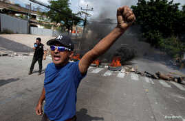 A demonstrator reacts near a burning barricade during a protest against government plans to privatize healthcare and education, in Tegucigalpa, Honduras, April 30, 2019.