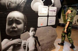 FILE - In this Sept. 7, 2010 photo, a South Korean soldier walks by a huge poster depicting North Korea's food crisis at the Korea War Memorial Museum in Seoul, South Korea. Two U.N. agencies warned May 3, 2019, that more than 10 million people in No...
