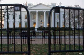The White House is seen behind security barriers in Washington, March 24, 2019.