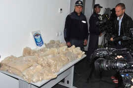 FILE - Bulgarian customs officers stand next to part of 712 kilograms of heroin, Sept. 29, 2018, the village of Kapitan Andreevo. The drugs were found in two Iranian trucks entering Bulgaria from Turkey. On April 18, 2019, prosecutors said Bulgarian ...